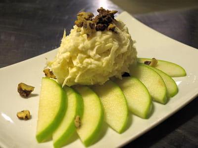 la salade de céleri est parsemée de noix et accompagnée de pommes granny.