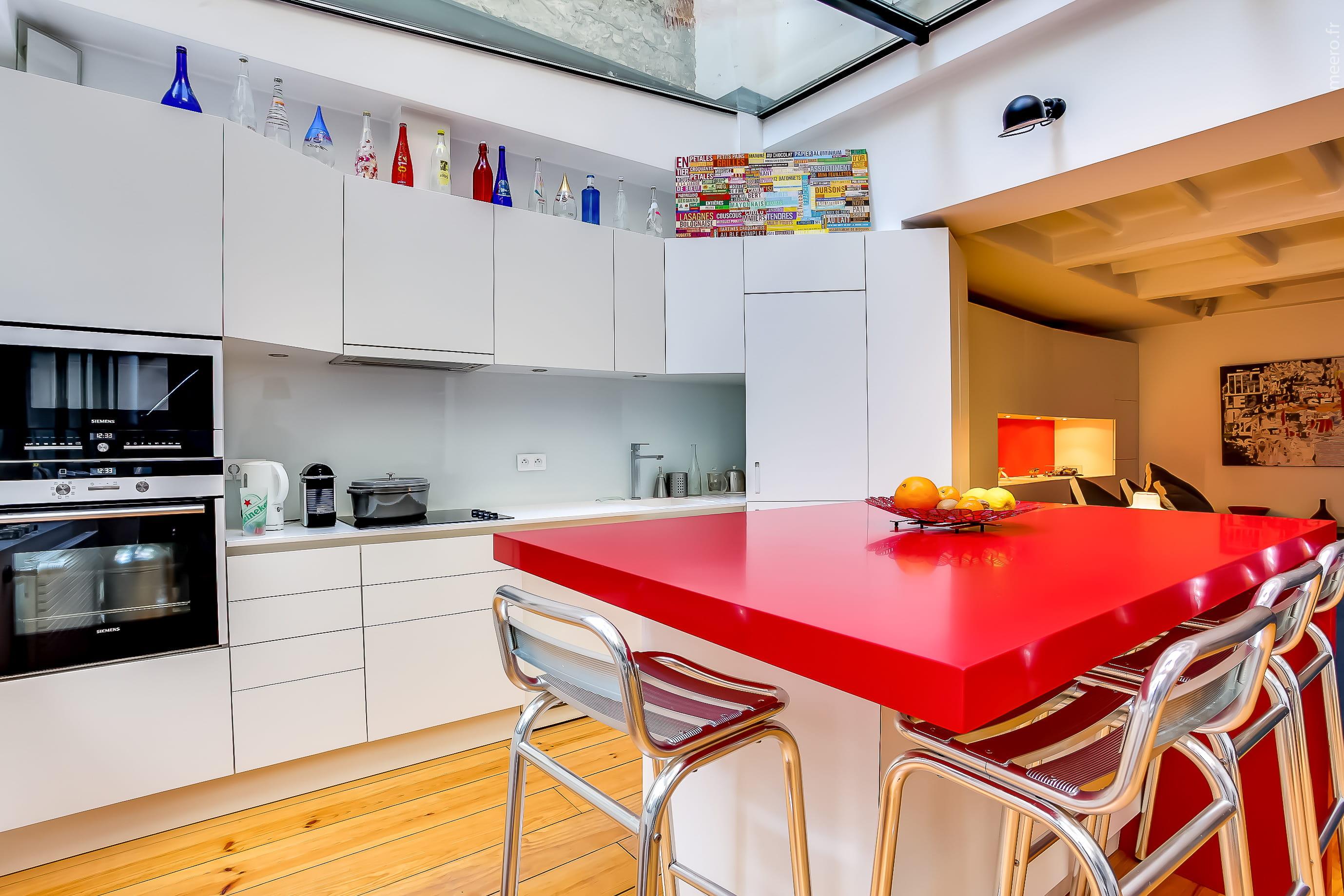 Une cuisine avec lot central for Cuisine rouge avec ilot central