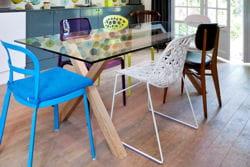 table en bois et verre entourée de chaises dépareillées