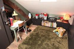 chambre aménagée avec un grand tapis, de nombreux rangements et des lampes