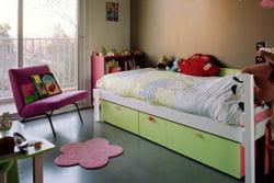 chambre avec lit composé de rangements et sol en béton lisse très facile
