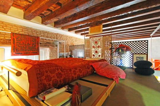 En hauteur, la chambre en mezzanine accentue le style oriental ...